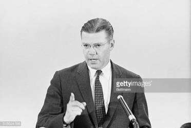 """(Original Caption) Defense Secretary Robert McNamara is shown here today at his press conference as he tells newsmen that 76,500 members of the Army, Navy, and Air Force reserve forces have been ordered to active duty by Oct.10. McNamara announced the action with the approval of President Kennedy. He said he could not say how long the National Guardsmen and organized reservists would have to serve on active duty because """"I can't predict the length of the (Berlin) crisis."""""""